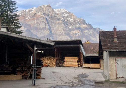 Holzlager vor beeindruckender Bergkulisse